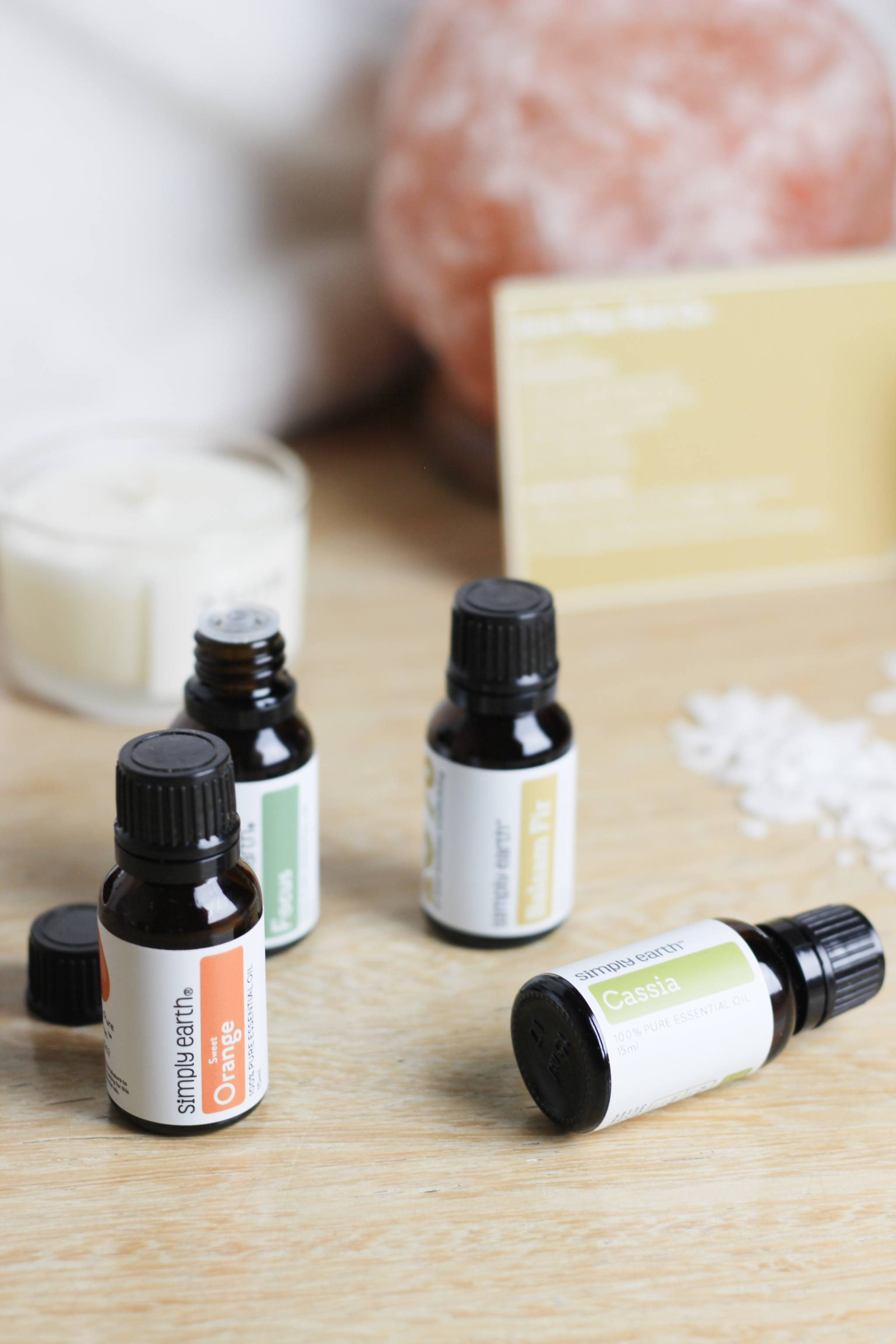 Simply Earth Bottles of Essential Oils in front of a Himalayan Salt Lamp