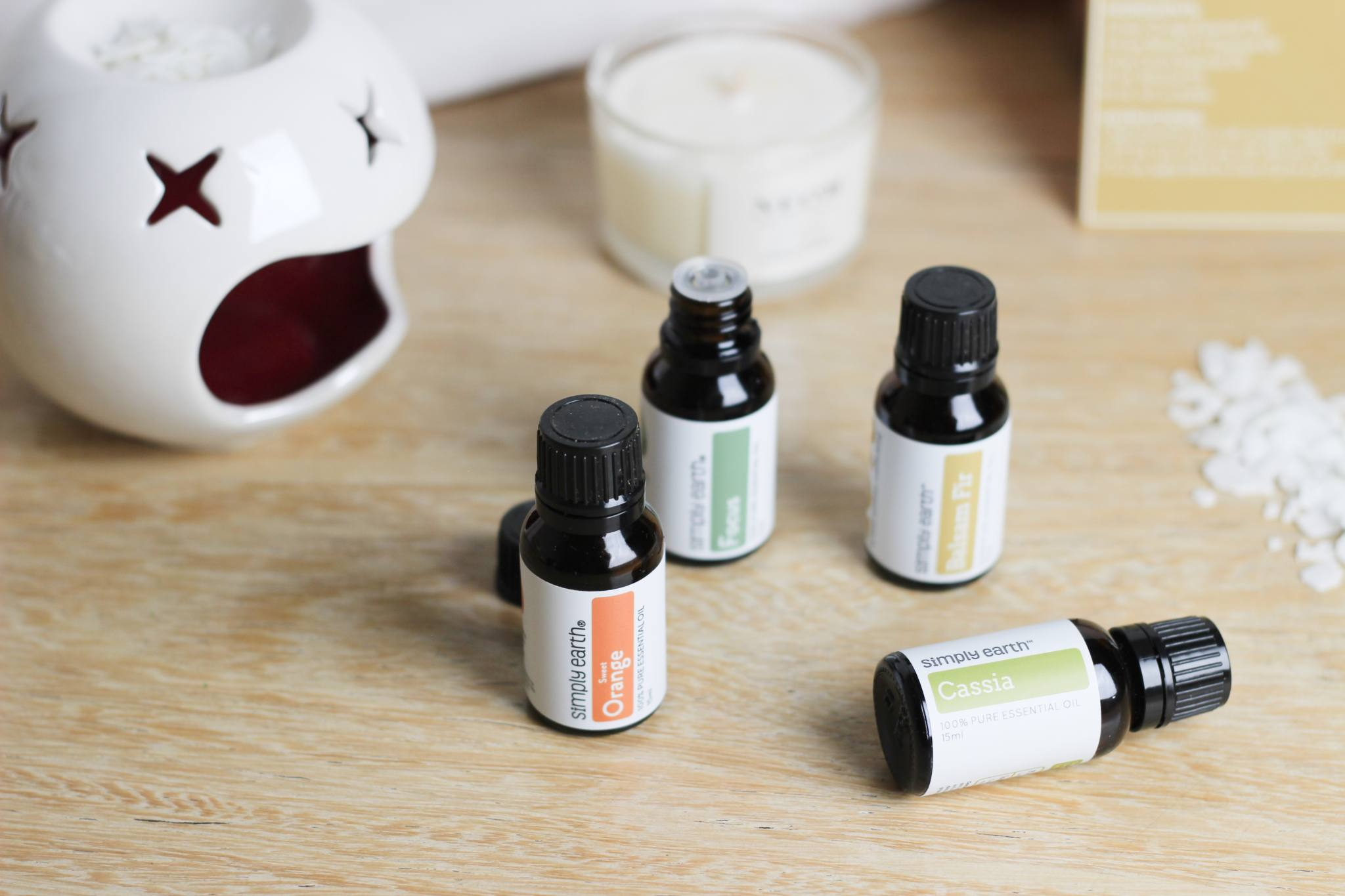 Simply Earth Bottles of Essential Oils in front of an oil burner and candle