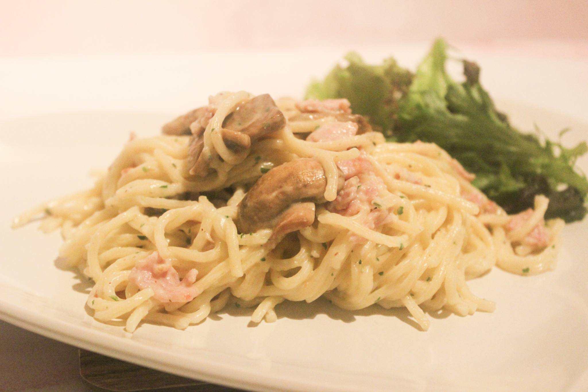 Spaghetti Carbonara prepared on a plate with a mixed leaf garnish