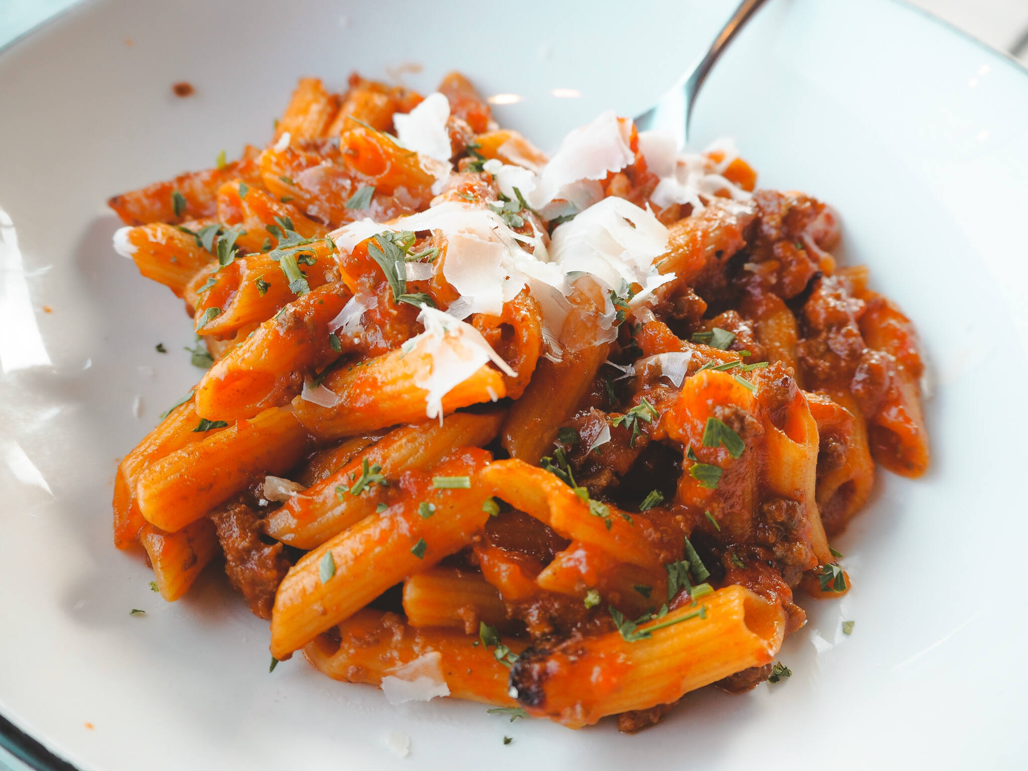 Penne bolognese pasta topped with cheese