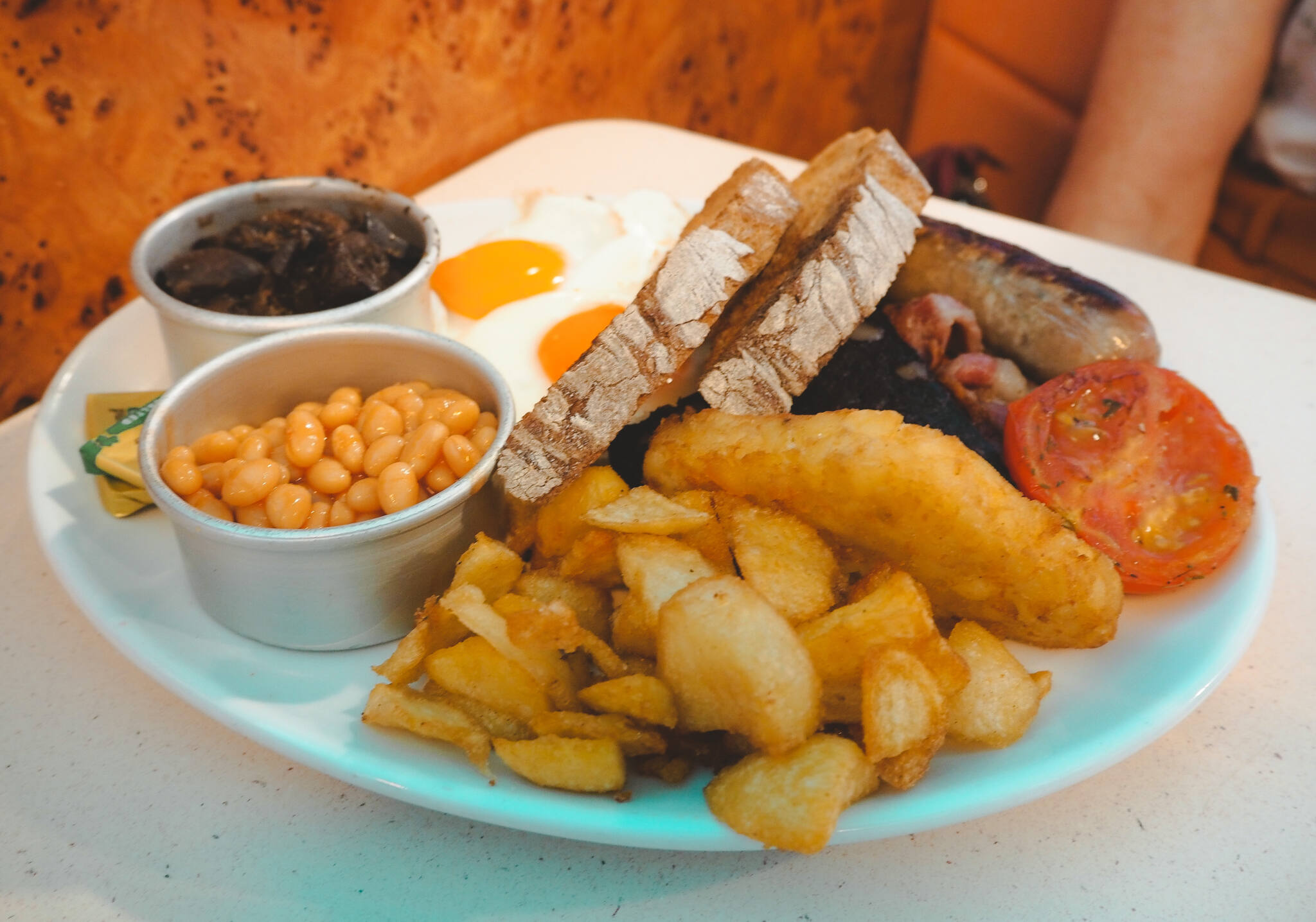 Full English Breakfast on plate with beans, garlic mushrooms, crispy potatoes, hash brown, fried eggs, toasts, tomato, sausage and bacon