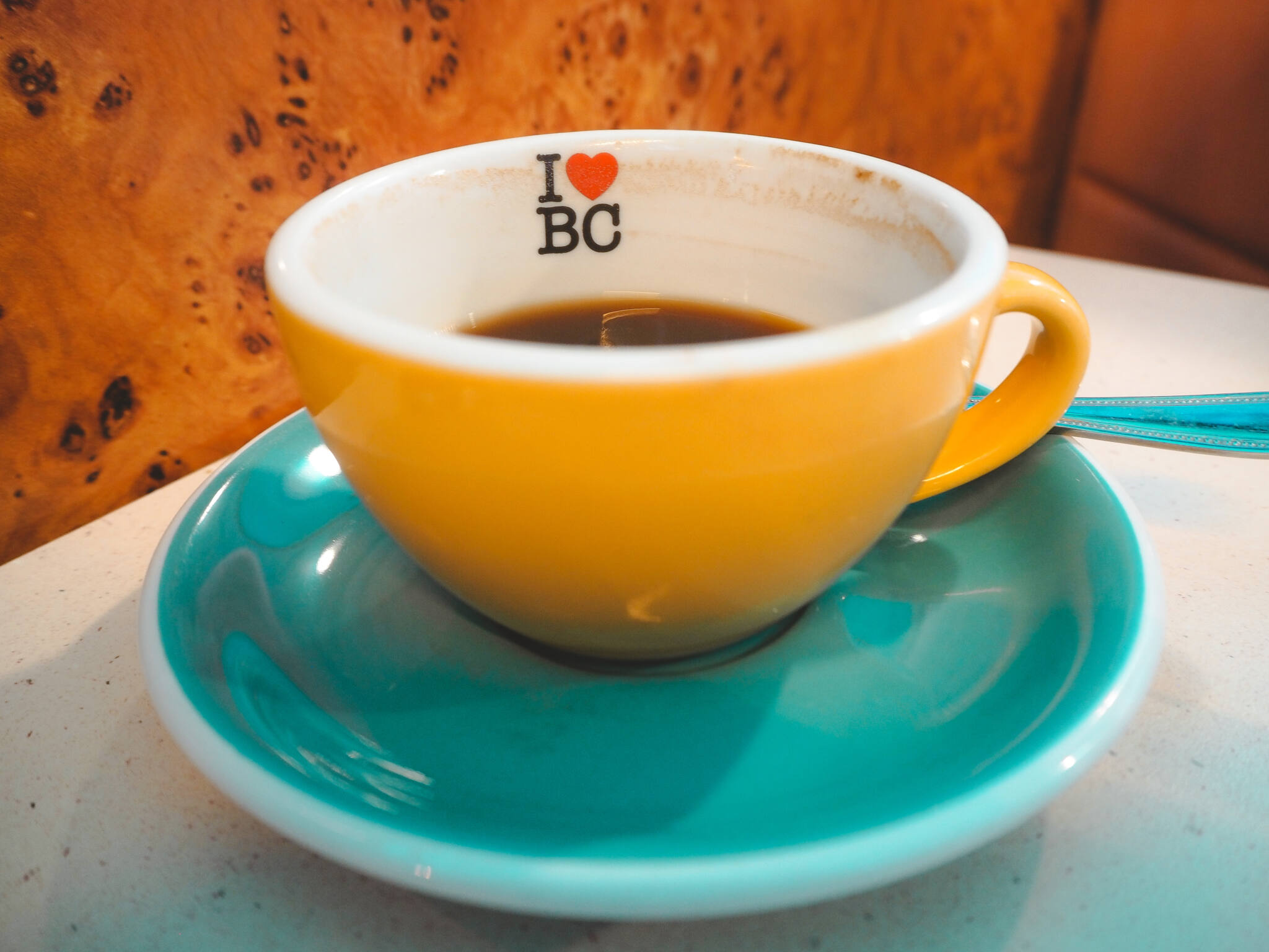 Yellow cup filled with black coffee and I Heart BC inside on blue saucer