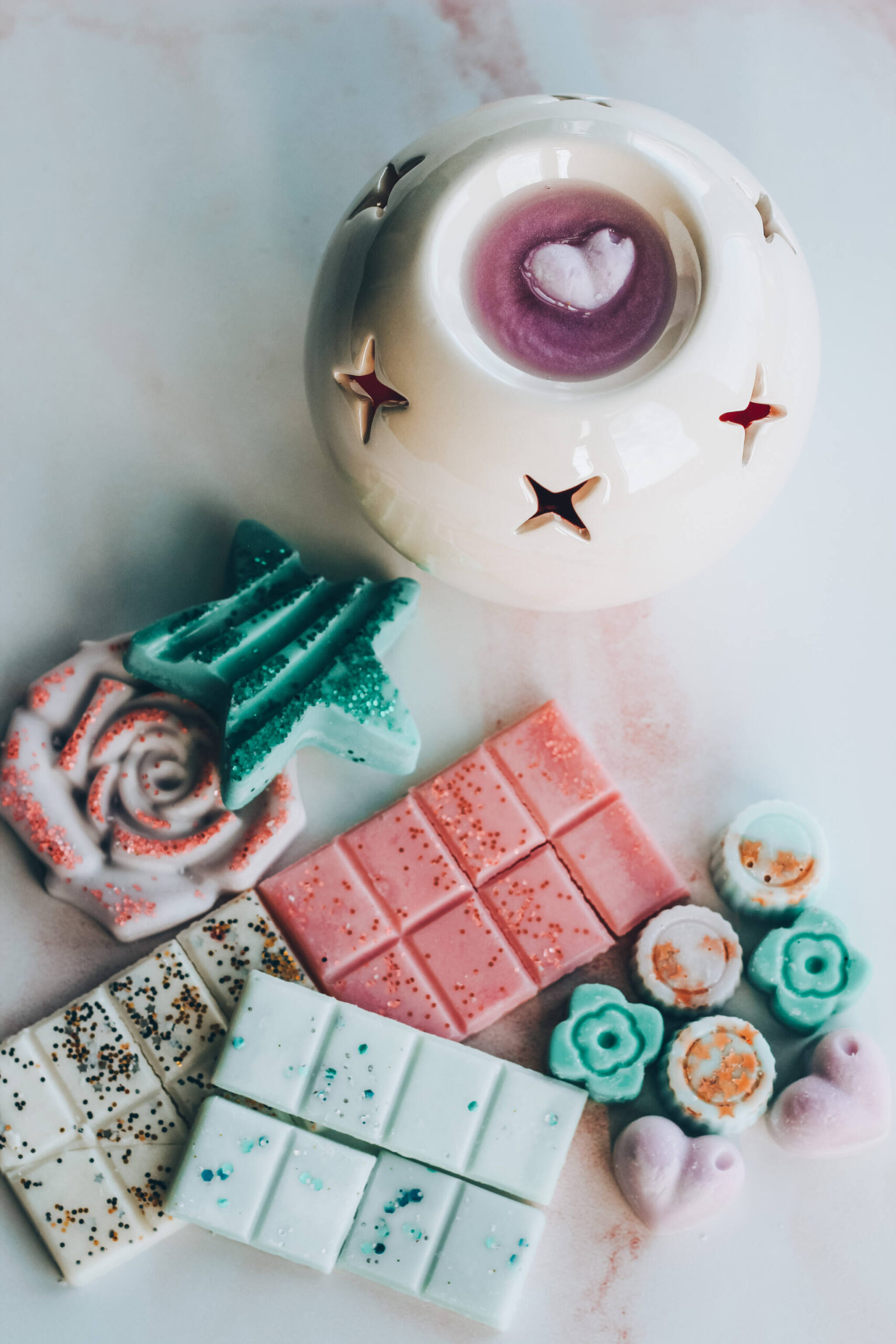 An assortment of wax melts in snap bars, minis, rose and star next to a wax melt melting in a burner