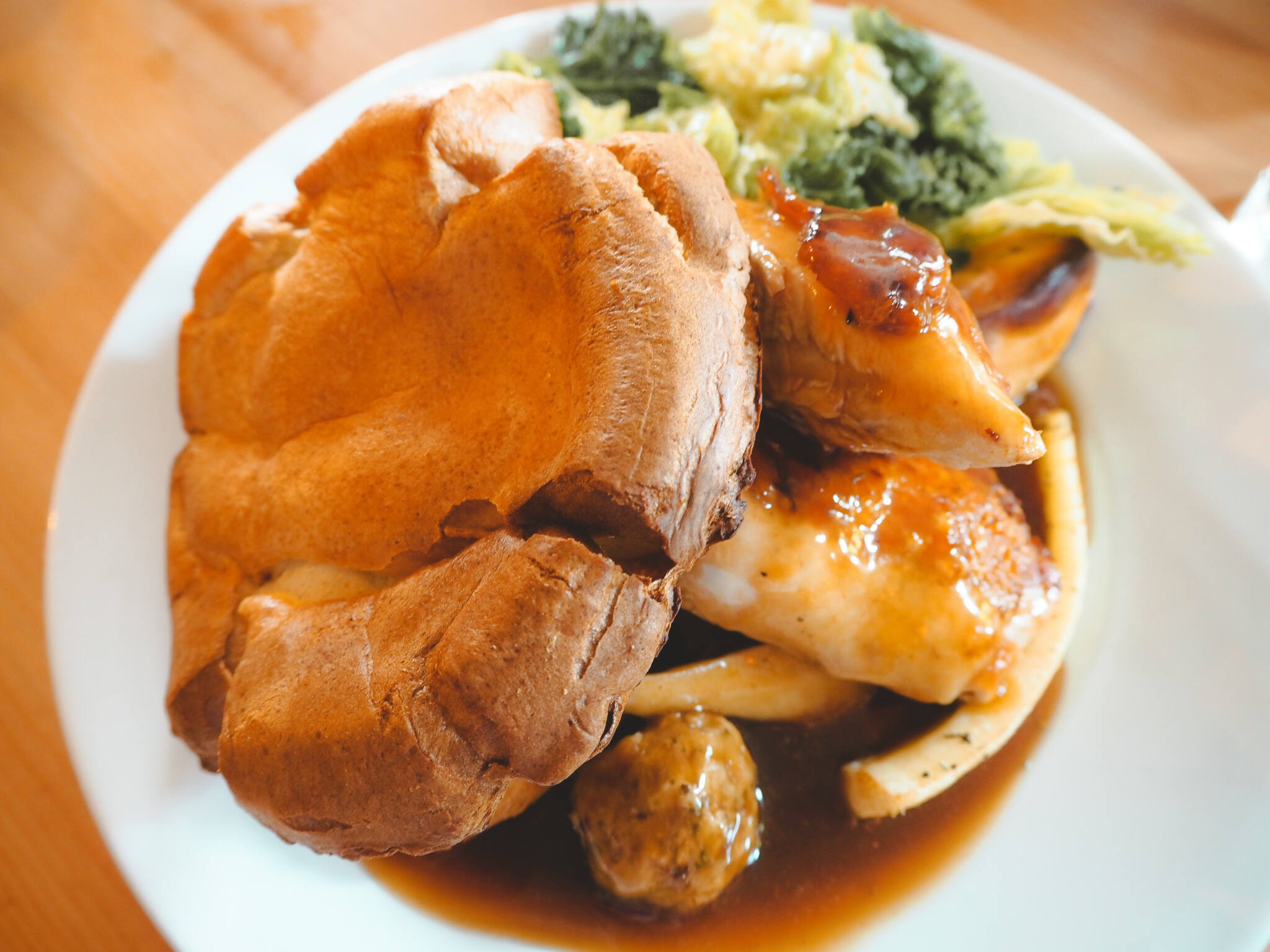 A plate of roast dinner showing yorkshire pudding, chicken, parsnips, stuffing and green vegetables served with lashings of gravy