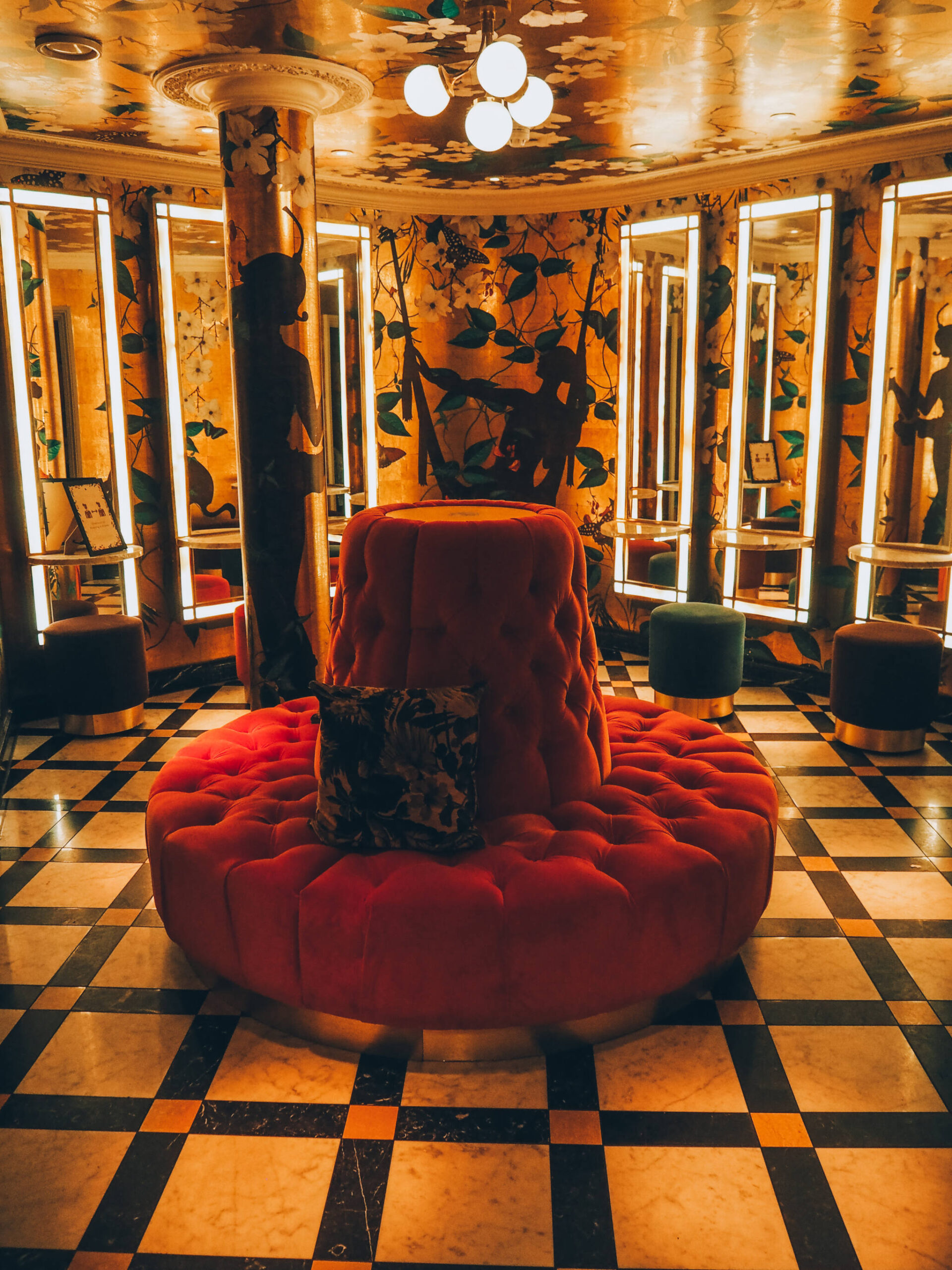 The Ivy bathroom with dressing room mirrors, lights and stalls and cushioned round chair in the middle