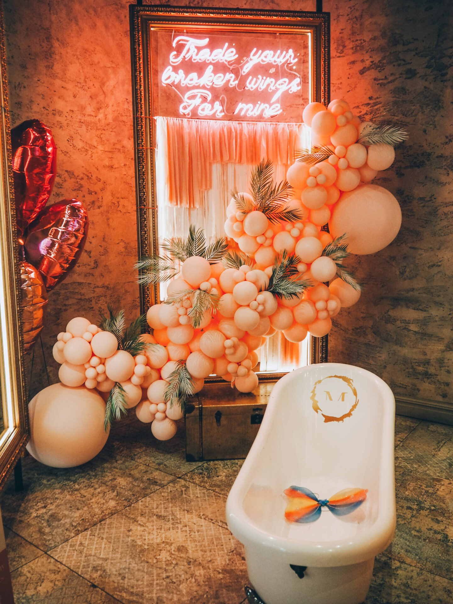 Menagerie roll top bath tub, neon sign saying 'Trade your broken wings for mine' and pale pink balloon arch